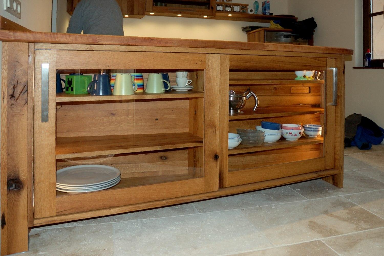 Altholzküche mit Kücheninsel mit Glasschiebetüren